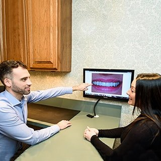 Dr. Ben Turnwald (dentist Schaumburg IL) talking to a patient about her smile.
