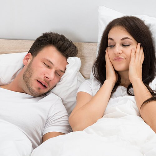 A snoring man and his wife annoyed and unable to fall asleep