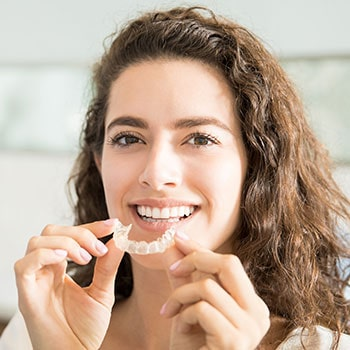 A female patient putting in Invisalign
