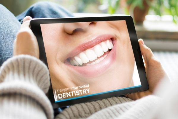 An iPad with a close-up smile on it for a virtual consultation